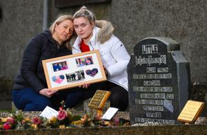 Hazel Gray and her daughter Rebecca holding a family picture at the graveside in Tempo Parish Churchyard, where both her parents and grandparents are buried.