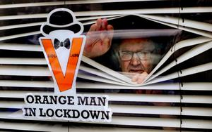 Orange Man, Randy Davidson, who is isolating at home, poses with a sticker in his window to celebrate the 12th of July as traditional large-scale parades were cancelled this year due to the pandemic. Picture by Niall Carson