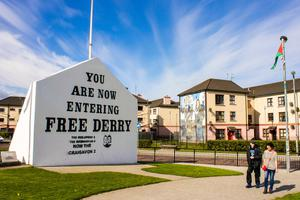 The 'You are Now Entering Free Derry' Corner in Londonderry, Northern Ireland, with two passersby
