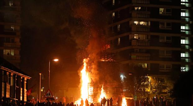 Crowds watch as a bonfire is lit in the New Lodge area of Belfast to mark the anniversary of the introduction of the controversial policy of internment without trial.