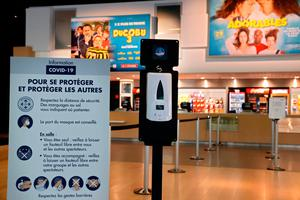 A dispenser of hydroalcoholic hand sanitizer gel is placed inside a movie theatre in Paris (Photo by THOMAS COEX / AFP) (Photo by THOMAS COEX/AFP via Getty Images)