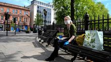 A woman, wearing a homemade face mask, relaxing in a very quiet Belfast city centre.