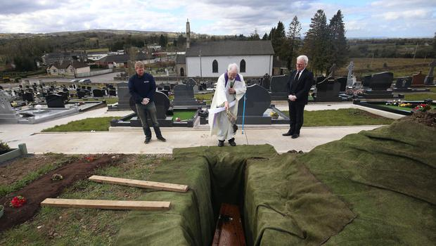 Parish Priest Gerard Alwill, performing the final committal over the coffin during the burial of Fermanagh's first Covid-19 victim Anne Best, 72 at St. Ninnidh's cemetary in Derrylin on Saturday.