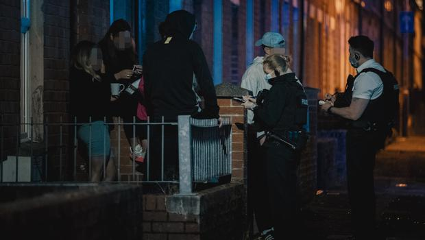 Police speak to young people outside a property in the 397,854 area of Belfast on February 22nd 2021 (Photo by Kevin Scott for Belfast Telegraph)